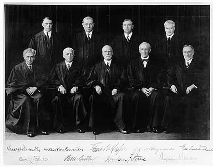 A group of men wearing black robes sit for the photograph.