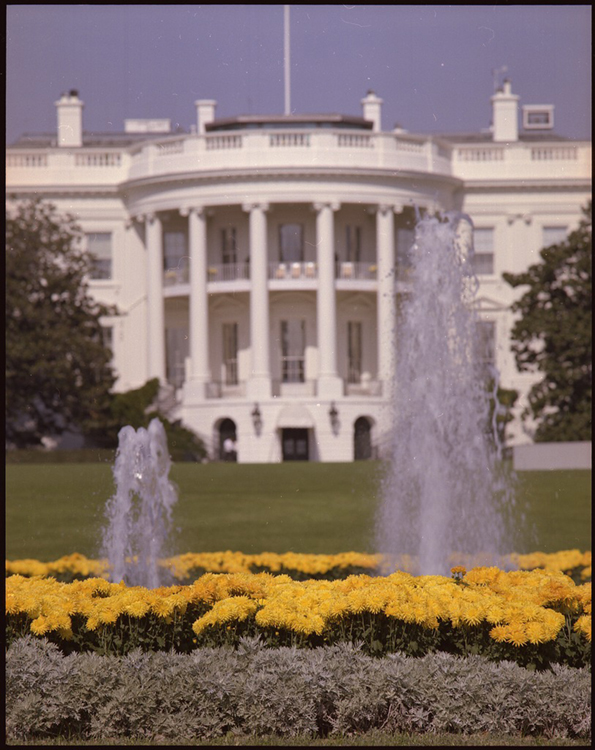 The White House and the fountains and gardens in front of it are shown.