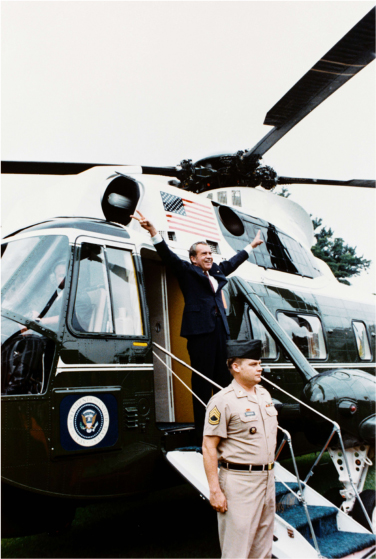 Nixon stands at the entrance to a helicopter with both hands outstretched, his fingers showing a peace sign.