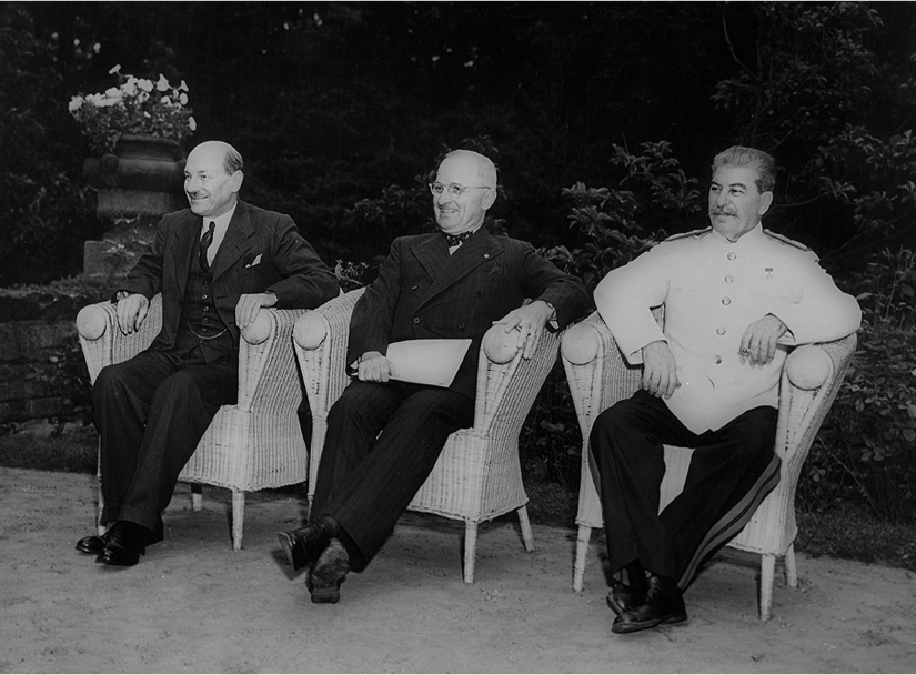 Harry Truman, Clement Atlee, and Joseph Stalin sit outside and smile.