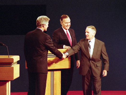 Ross Perot shakes hands with Bill Clinton. President Bush stands beside Perot.
