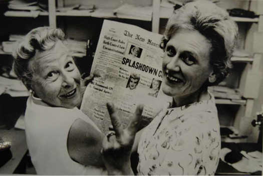 Estelle Griswold and Ernest Jahncke smile as they hold a newspaper with the headline