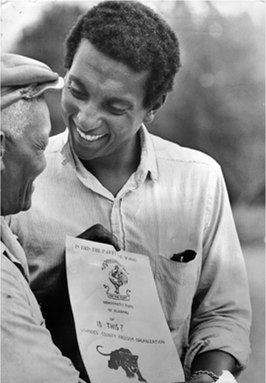 Stokely Carmichael smiles and gives a flyer to another man. At the bottom of the flyer is the Black Panther logo.