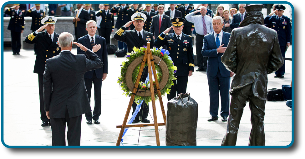 A photograph shows several key members of the United States military accompanied by a crowd as they stand facing toward a wreath. All hold their right arms in salute or placed across their chests.