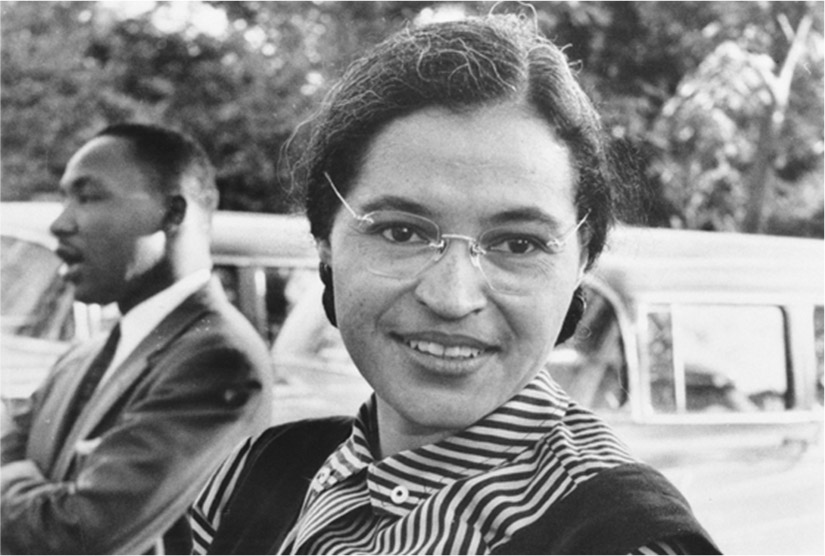 Rosa Parks sits outside. Martin Luther King Jr. sits in the background.