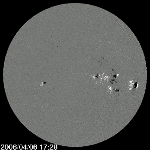 A magnetogram of the sun, which appears as a gray disc against a black background, with white and black spots scattered on it. Most of the spots are concentrated in the center right part of the image.