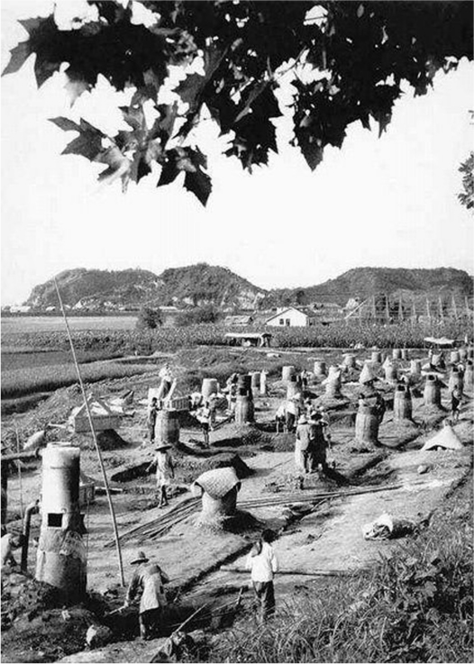 Part of a field is cleared for rows of furnaces. Multiple people work the furnaces. A neighbor's house and field is visible.