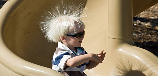 A child swoops down a plastic playground slide, his hair standing on end.