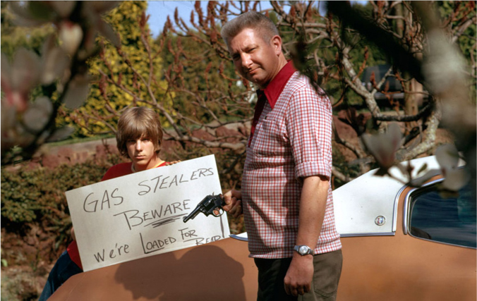A man holds a gun and a boy holds a sign that reads,
