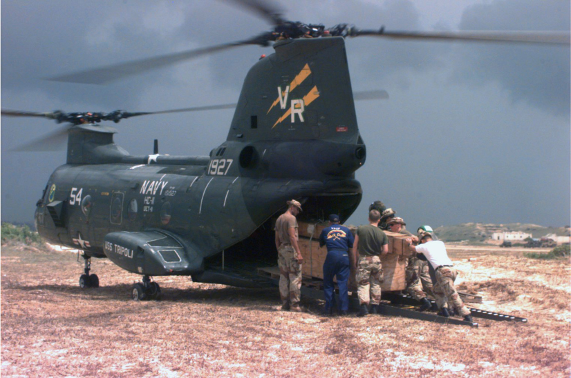 Soldiers load cargo into the back of a Navy helicopter.
