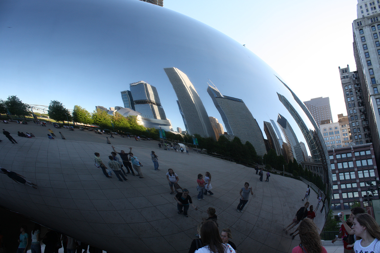 A photo shows the large, extremely smooth and reflective bean shaped sculpture. The city skyline reflects in the bean's surface.