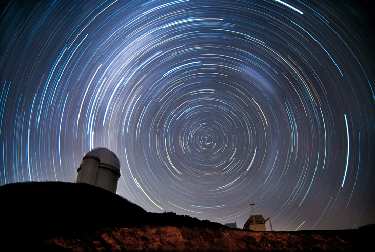 Photograph of Stars Circling the South Celestial Pole. In this time-exposure photograph the stars are not seen as points of light, but as semi-circular arcs due to the rotation of the Earth during the exposure. The domes of several telescopes are silhouetted against the sky.