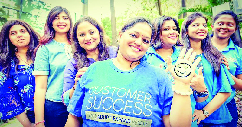 "The image shows seven women smiling. The one in the center is wearing a shirt that says ""Customer Success."""