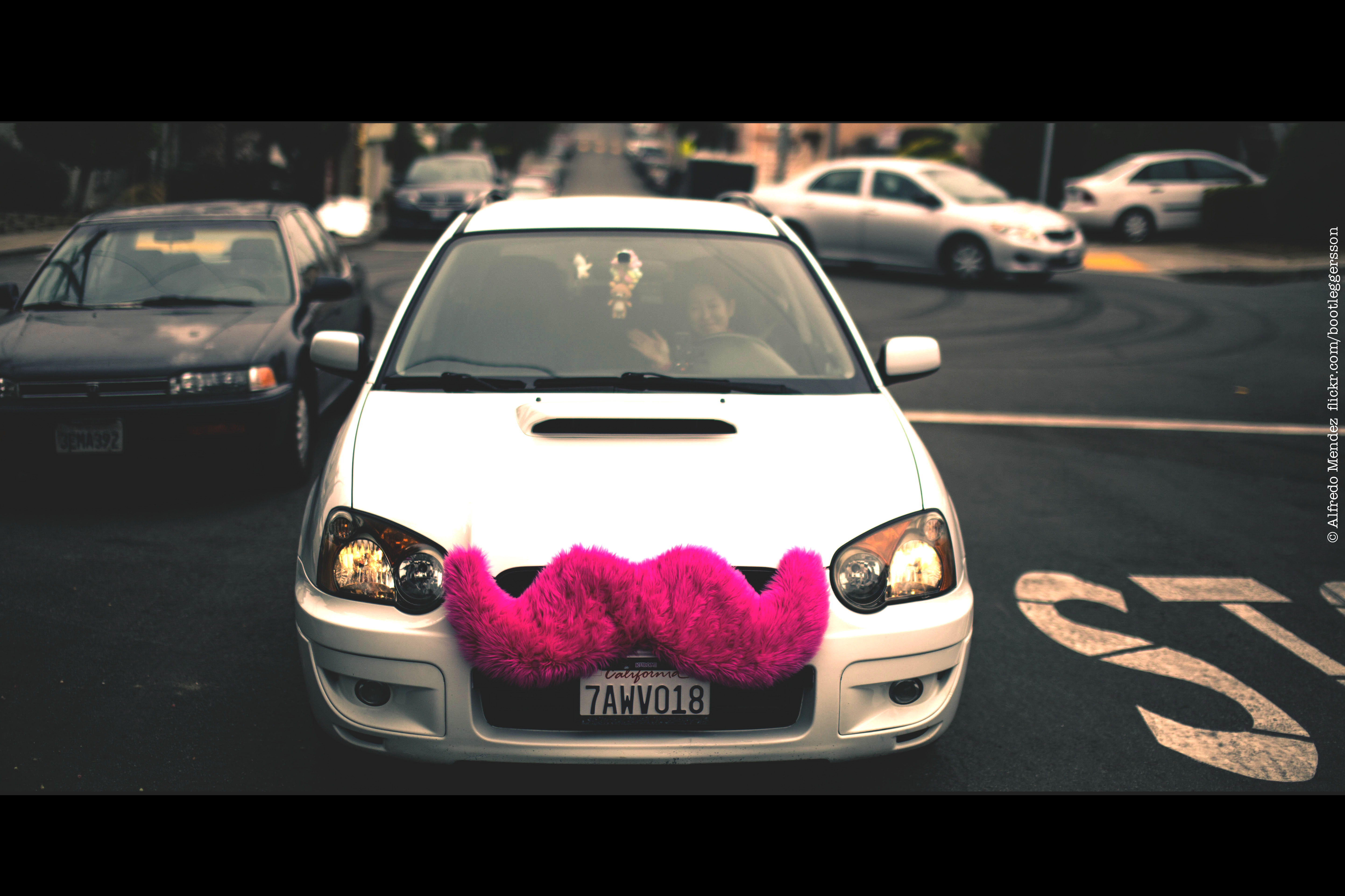 A photograph shows a car with a large, fuzzy, pink moustache attached to the front grill of the car.
