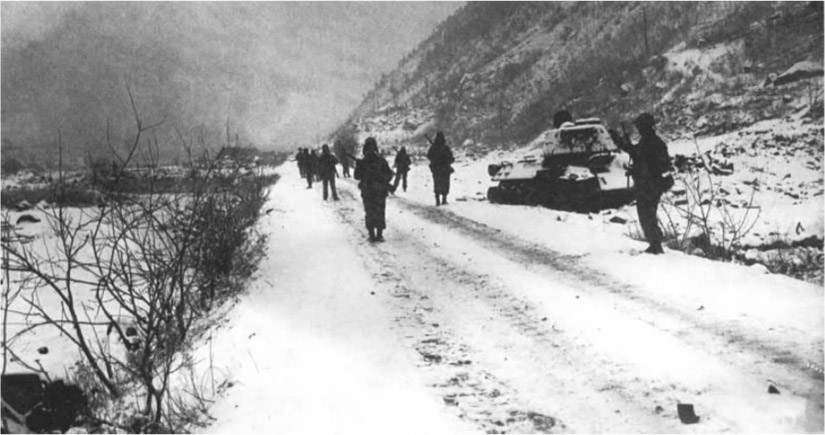 Soldiers spread out and walk up a snowy road. A tank sits on the side of the road.