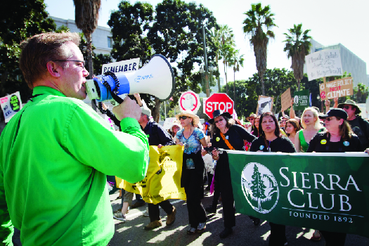 "An image of a person speaking through a bullhorn on the left, and a crowd of people marching down a street on the right. Several marchers are holding a large banner that reads ""Sierra Club""."