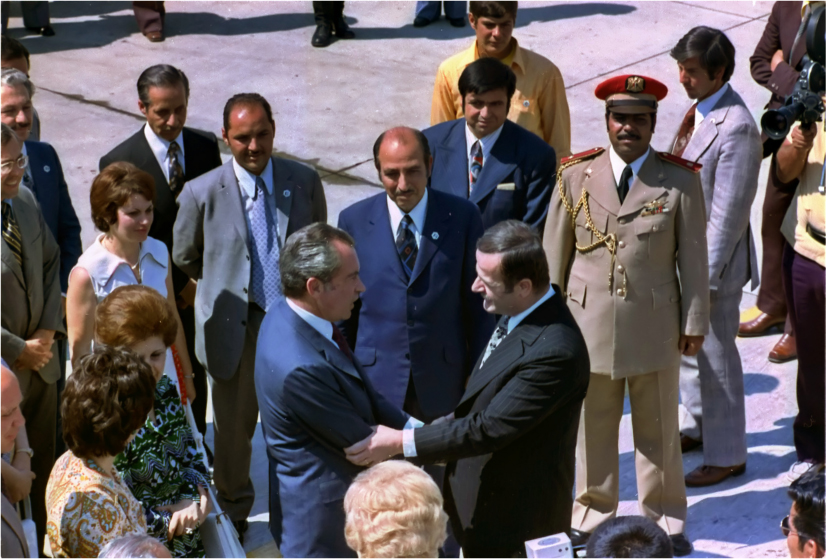 President Nixon and President Hafez al-Assad shake hands in the middle of a group of Americans and Syrians.