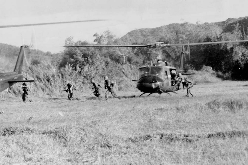 Men run out of a helicopter that has landed in a field.