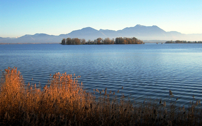 Water surface of a river is shown, with mountains in the background. There are small ripples over the water surface.
