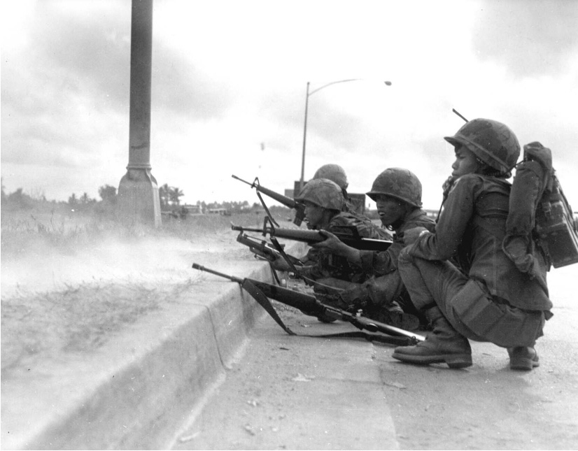 South Vietnamese soldiers crouch on the road and prop their guns on the curb.