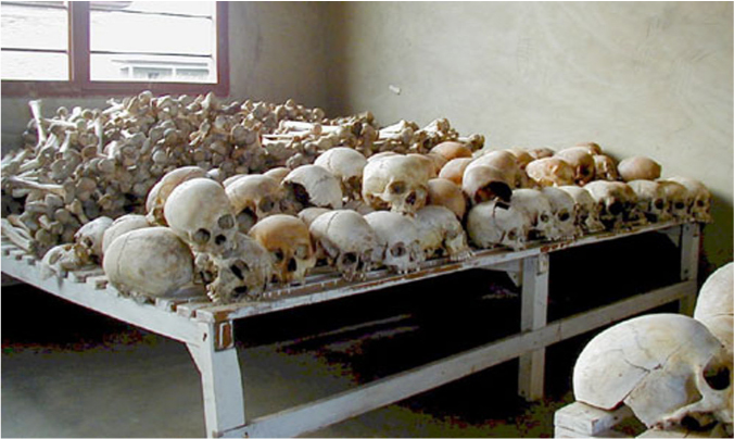 Piles of skulls and bones cover a table. Deep gashes are seen on several of the skulls.