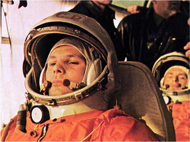 Yuri Gagarin wears his astronaut uniform and helmet and sits on a bus. Another astronaut, his cosmonaut, sits behind him.
