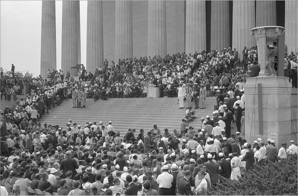 A crowd surrounds the steps of the Lincoln Memorial. Inside the opening is a military color guard, a podium, and different speakers. Cameras surround the crowd.