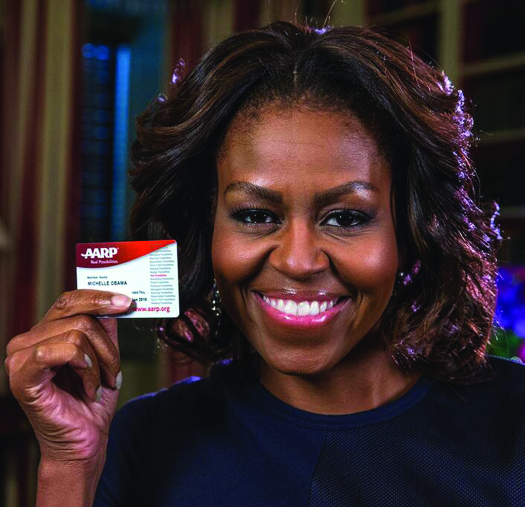 An image of Michelle Obama holding an AARP membership card.