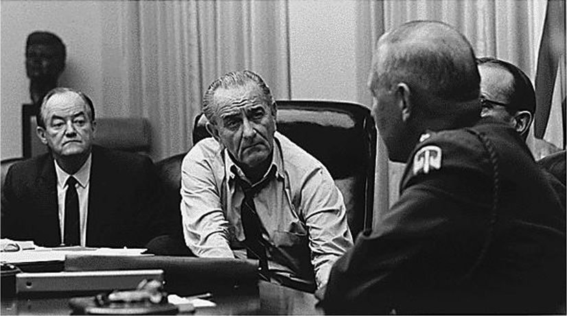 President Johnson and Vice President Hubert Humphrey sit at a table with other leaders and discuss.