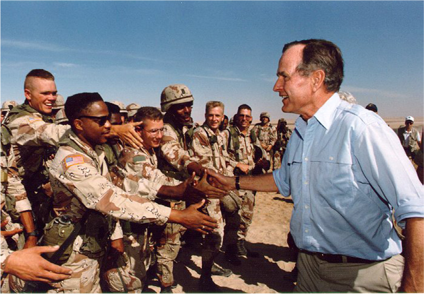 President George H. W. Bush shakes hands with U.S. soldiers.
