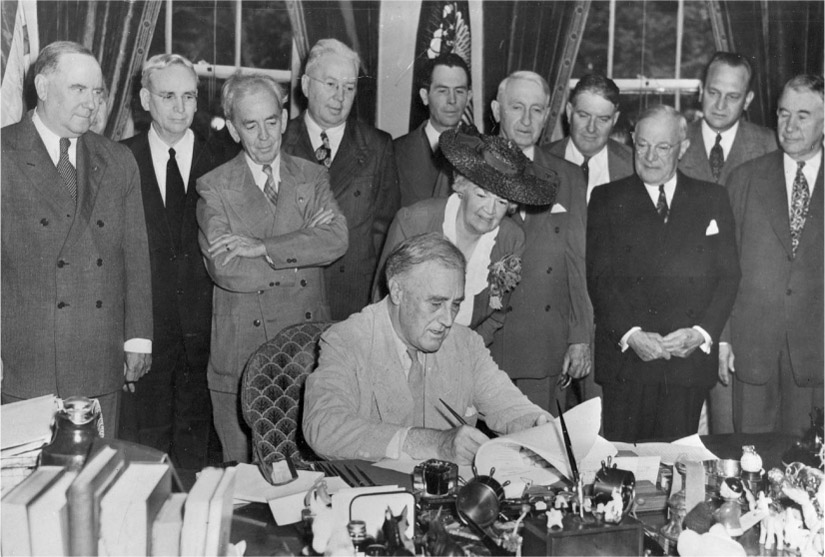 President Franklin Roosevelt sits at a desk and signs a document. A group of people stand behind him.