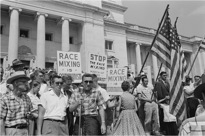 A group of people stand in front of the Arkansas state capitol and hold American flags and signs that read