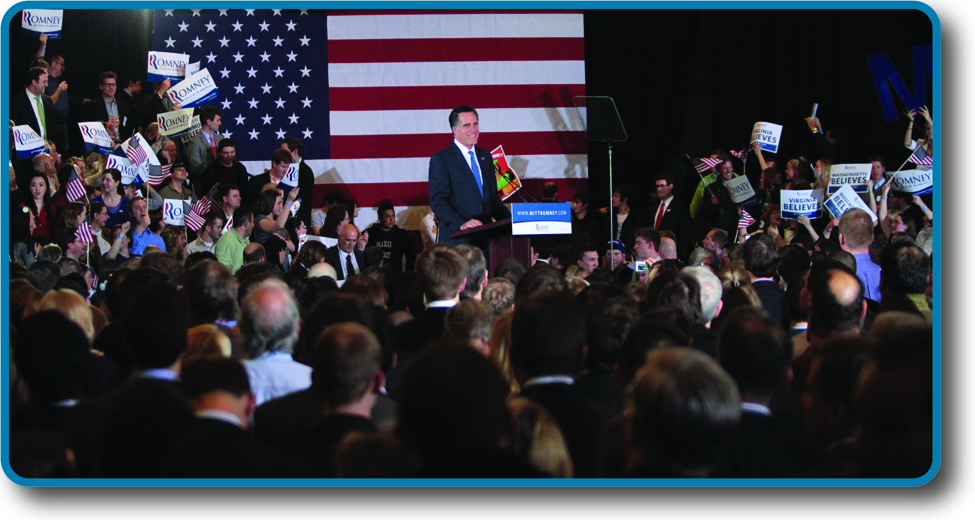 Photo of Mitt Romney in front of a crowd, smiling.