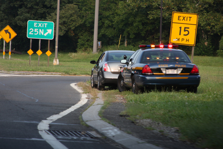 The image shows a state police car that has pulled over another car near a highway exit.