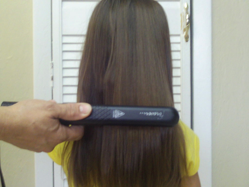 A hair straightener is being used on a girl's long dark hair. A large section of the hair is sandwiched between the two flat irons of the hair straightener, which is moved down the hair, applying heat.