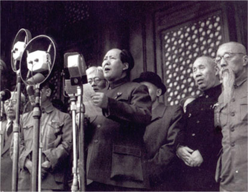 Mao Zedong delivers a speech on stage in front of many microphones. Other Chinese leaders stand behind him.