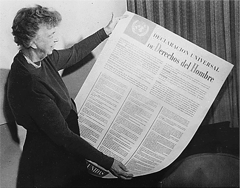 Eleanor Roosevelt holds a poster of the Universal Declaration of Human Rights in Spanish.