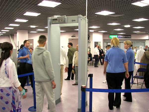 Photograph of people queued up at a metal detector gate at an airport.