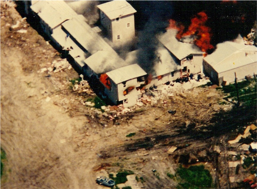 An aerial shot of the compound on fire. Flames are seen coming out of windows. Black smoke fills the air.