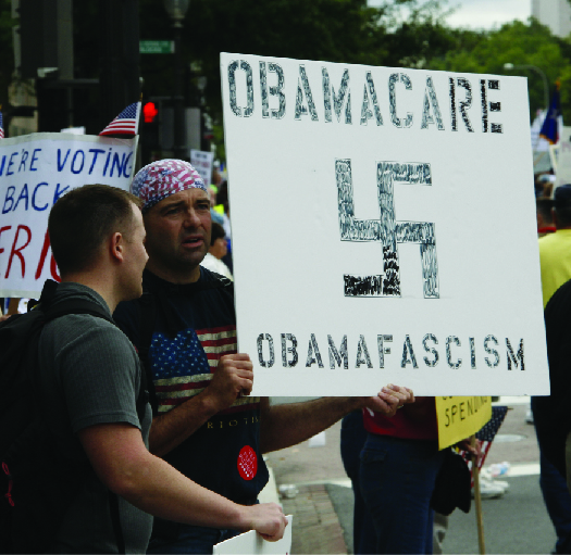 """An image of a person holding a sign that reads """"Obamacare obamafascism"""" and has the symbol of a swastika."""