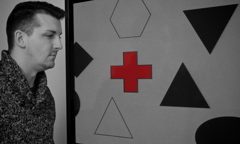 A photograph shows a person staring at a screen that displays one red cross toward the left side and numerous black and white shapes all over.