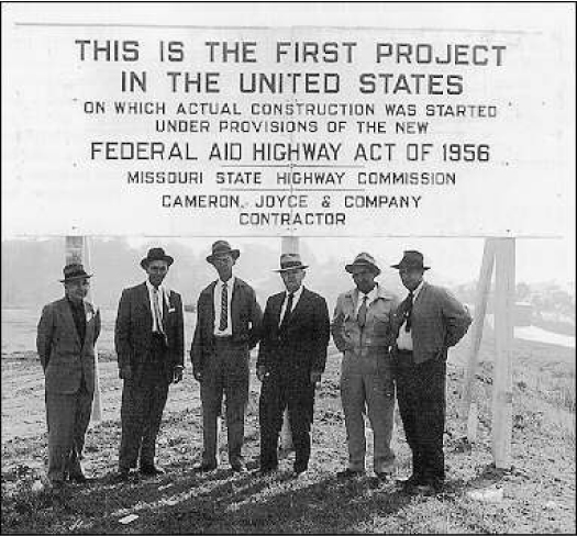 "A group of men stand under a sign that reads ""This is the First Project in the United States on which actual construction was started under provisions of the new Federal Aid Highway Act of 1956. Missouri State Highway Commission. Cameron, Joyce, & Company Contractor."""