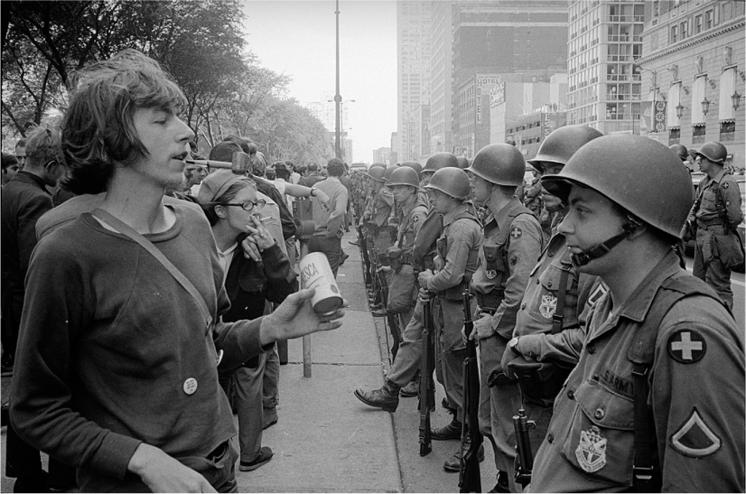 Rows of National Guard soldiers stand in the street and face protesting civilians.