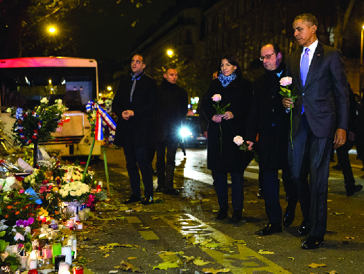 An image of Barack Obama, François Hollande, and Anne Hidalgo laying roses at a makeshift memorial.