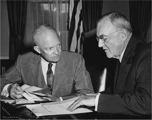 President Dwight D. Eisenhower and John Foster Dulles sit next to each other at a desk and talk.