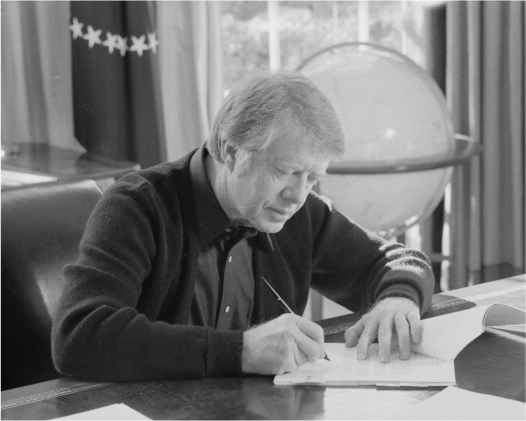 Jimmy Carter sits at a desk and signs a document.