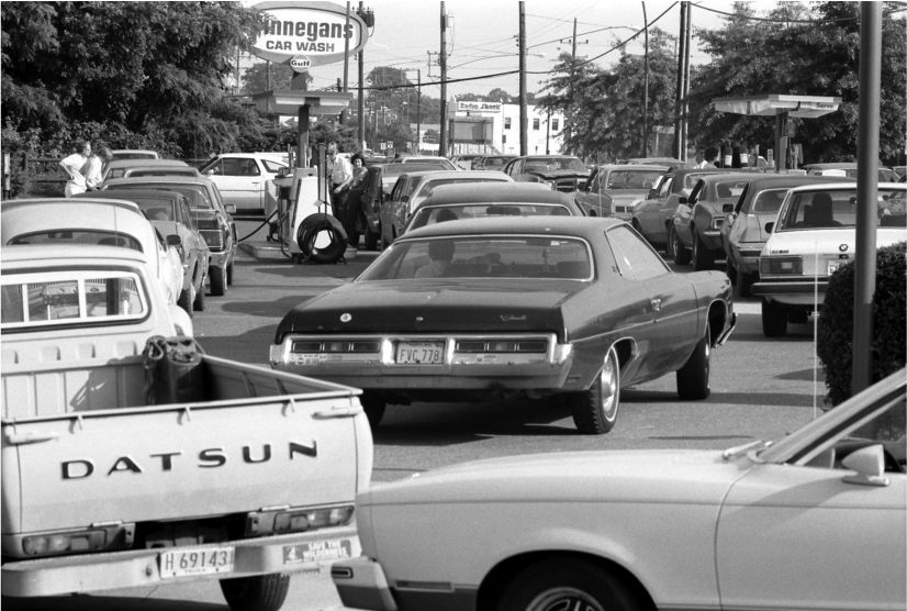Cars line up in and around a gas station to use a pump.