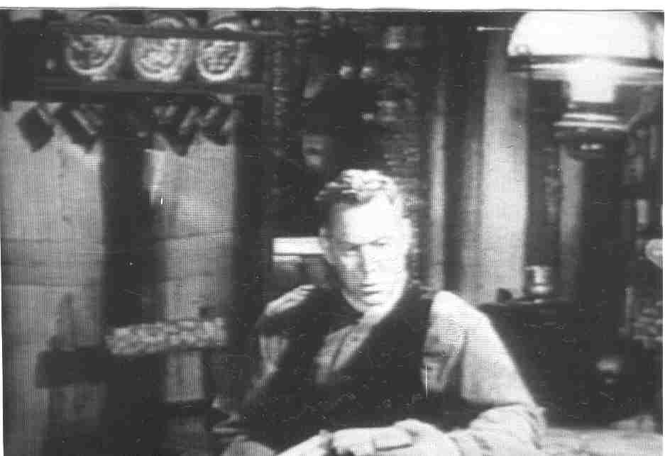 A film screenshot of a man sitting at a table inside a home with decorations in the background.