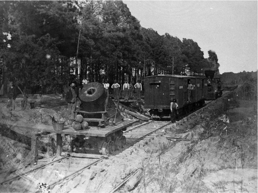 The photograph shows a mortar gun on wheels in front of a train.