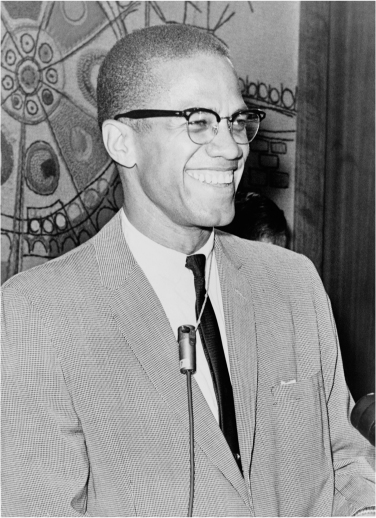 Photograph of Malcolm X smiling and standing behind a microphone.